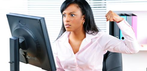 Angry young black business woman punching computer in office