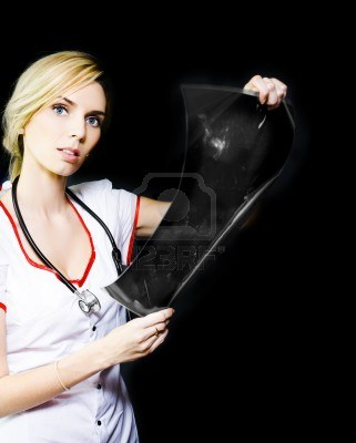13453498-pretty-young-nurse-isolated-on-a-black-background-studying-a-patients-xray